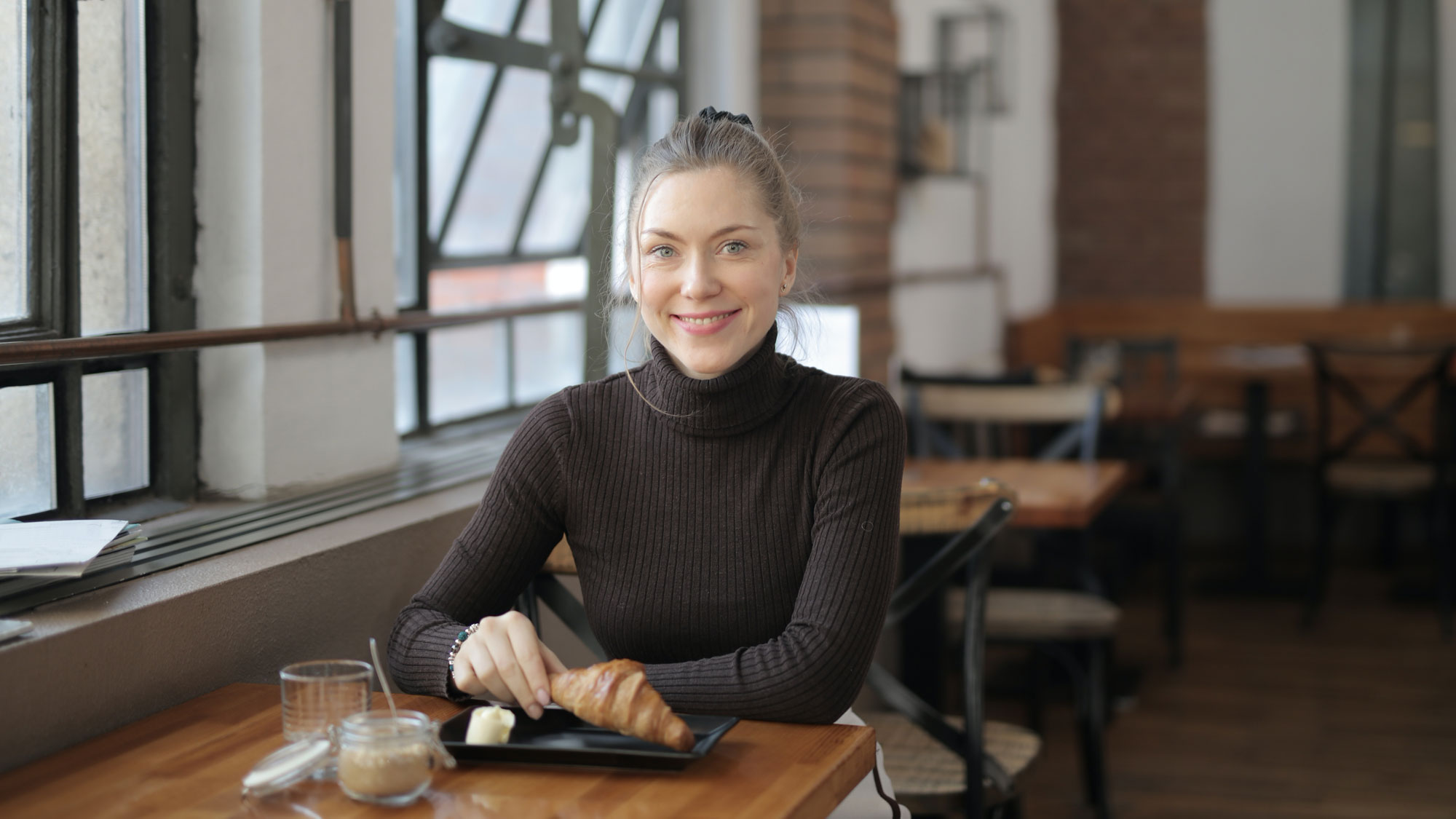 woman-in-black-turtleneck-sweater-holding-a-croissant-3906941